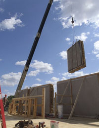 Pre-fab straw bale wall lifted into place