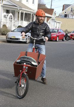dad with baby in car seat in cargo bike